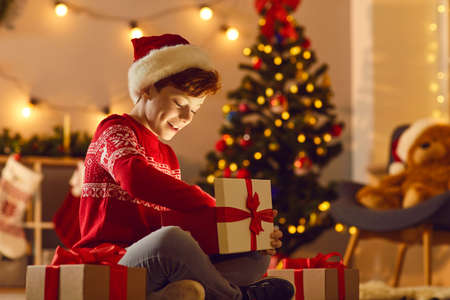 Surprise from Santa Claus. Happy excited boy sits on the floor in a cozy room and opens a Christmas present and excitedly looks at the magic light in the box. Christmas background.