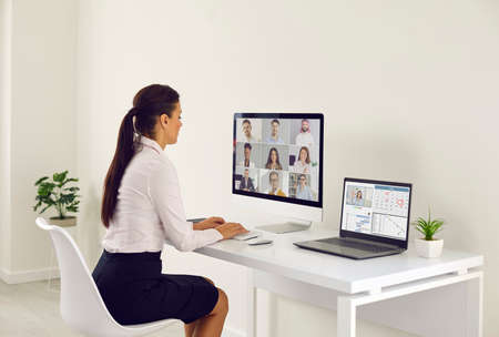 Young female worker sitting in front of modern desktop and laptop computers at office desk and typing message in online chat during virtual work meeting with diverse team of her business colleagues