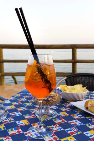 Traditional Italian Spritz cocktail against Taormina, Sicily, Italy Stock Photo