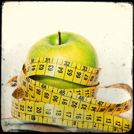 Green apple with measuring tape on white background photo