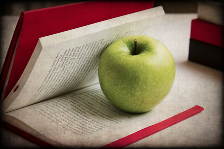 Fresh Green Apple Isolated on an open book photo