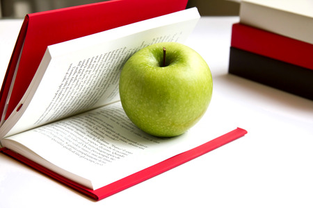 Fresh Green Apples Isolated on a open book photo