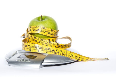 weighs: Green apple with measuring tape and weighs food on white background Stock Photo