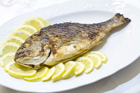 sea bream: Grilled sea bream with lemon slices on white plat