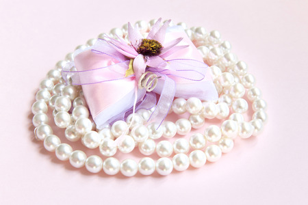 comfits: Pack with sugared almonds with pearl necklace on a pink background