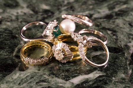 faceting: Precious jewels, rings with diamonds, emeralds and corals on green marble Stock Photo