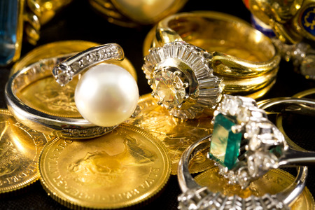 faceting: Precious jewels, rings with diamonds, emeralds and corals on pounds in gold