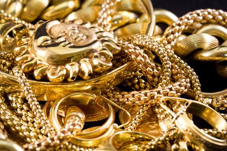 Close-up van gele gouden sieraden op een zwarte achtergrond Stockfoto