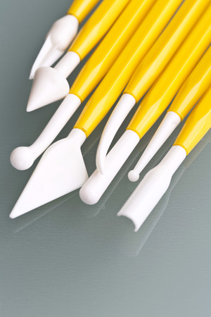 pasta di zucchero: Strumento per la pasta di zucchero modellazione su uno sfondo in legno Archivio Fotografico
