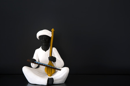 lute: Statue depicting a lute player on a black background