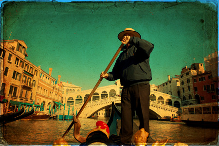 Gondolier on a gondola on the Grand Canal in Venice. Gondola's are a major mode of touristic transport in Venice, Italy. Stock Photo - 28811218