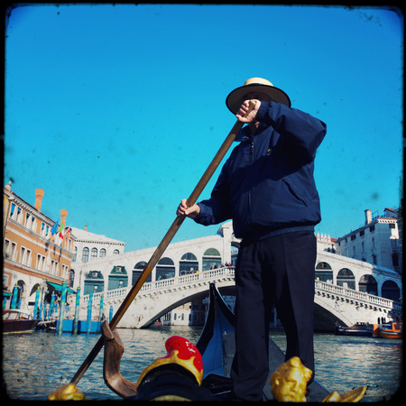 Gondolier on a gondola on the Grand Canal in Venice. Gondola's are a major mode of touristic transport in Venice, Italy. Stock Photo - 28811220