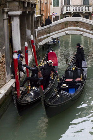 Gondolier on a gondola on the Grand Canal in Venice. Gondola's are a major mode of touristic transport in Venice, Italy. Stock Photo - 28811227