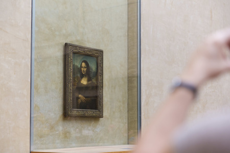PARIS, FRANCE, August 6, 2014: People waiting on queue to see the Mona Lisa painting at the Louvre Museum (Musee du Louvre) on August 6, 2014 in Paris, France.