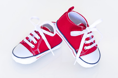 new born baby boy: A pair of red baby shoes on a white background