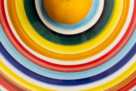 clementine: Clementine orange isolated on a multicolored dish Stock Photo