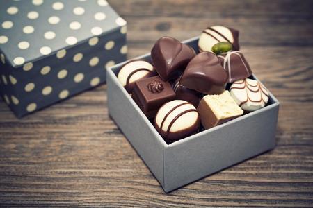 Bombones de chocolate clasificados en un fondo de madera Foto de archivo