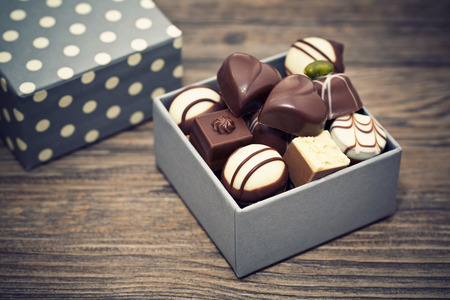 praline di cioccolato assortiti su uno sfondo di legno Archivio Fotografico