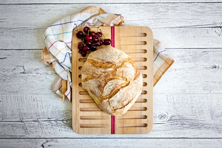 slicer: Homemade bread on bread slicer on a wooden background