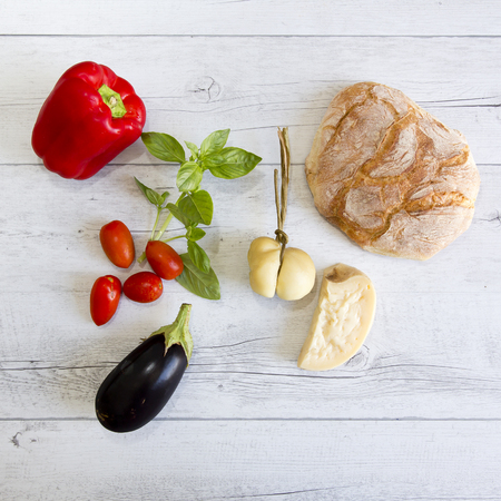 caciocavallo: A red pepper, a branch of basil, cherry tomatoes, aubergine and bread on wooden background