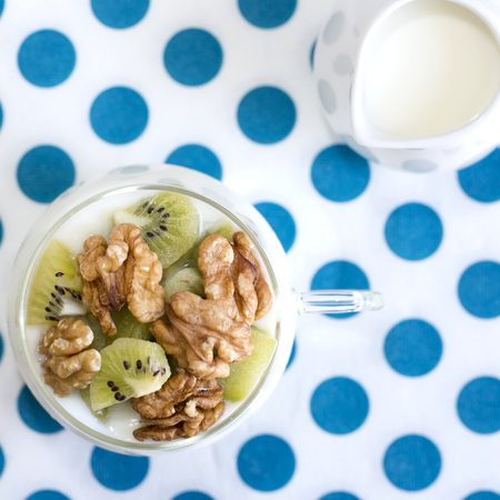 the milk jug: Plain yogurt with kiwi and nuts with milk jug on a wooden background