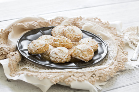 Coconut biscuits with icing sugar over pewter plate and varied doilies