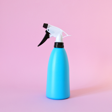 Spray bottle for plant care. Isolated on pink background