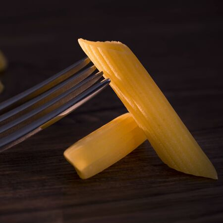 Penne pasta raw on wooden background
