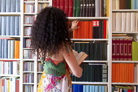 Girl starts from behind looking for books in the library at home