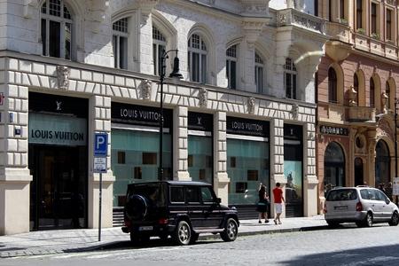 louis vuitton: Praque, Czech Republic – May 31, 2014   Shoppers passing by a Louis Vuitton boutique on the most elegant street in Praque - Paris street