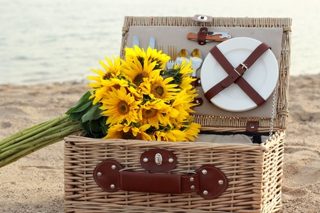 Picnic basket and sunflowers on the beach