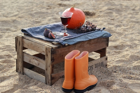 rain boots: Autumn scenery with pumkin and rain boots in the box after the wine on the beach