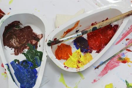 alumnos en clase: pinturas de colores y pincel en contenedores de pl�stico Foto de archivo