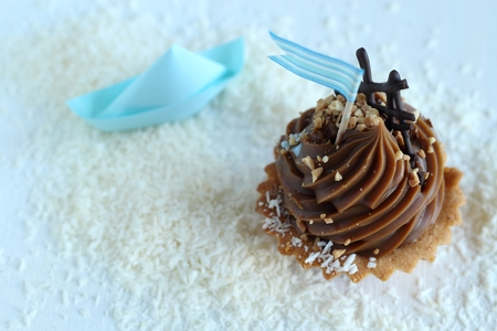 desiccated: caramel cupcake with blue flag on desiccated coconut