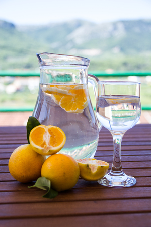 Water with fresh oranges on the terrace