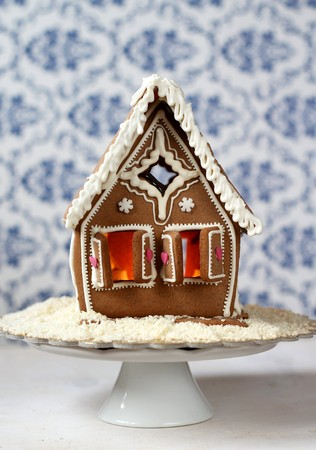 Traditional gingerbread house with lit candle inside