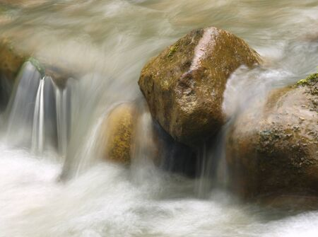 Small waterfall in the mountain river. Beautiful natural background of stones and with flowing, blurring water and foaming.