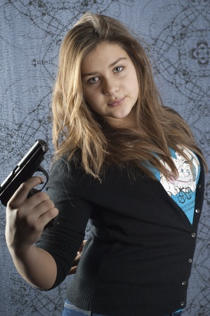 spy girl: Girl with a weapon on abstract background Stock Photo