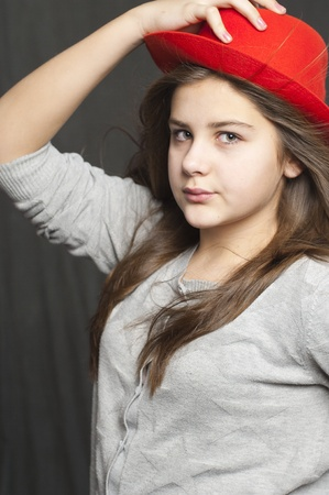 Girl with hat. Grey  wall background. Studio work photo