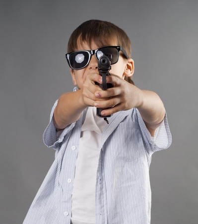 Boy with a handgun. Studio work Stock Photo - 12063640