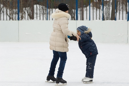 Young girl help a little kid skating  This is the first time he on the skates Stock Photo