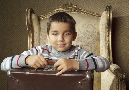 Little kid sits in a chair and hold a suitcase photo