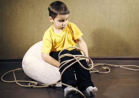 Tied up kid sit on a floor photo