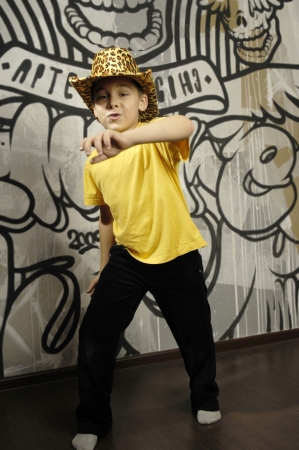 Little kid dancing near the abstract wall Stock Photo