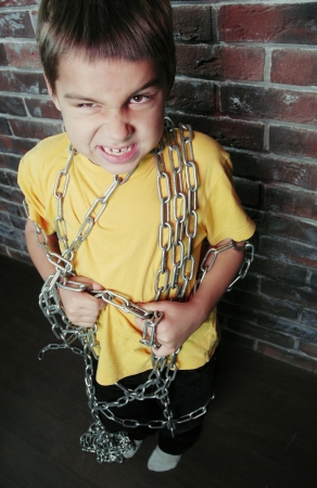 Angry child prisoner with chain trying to pull it off photo
