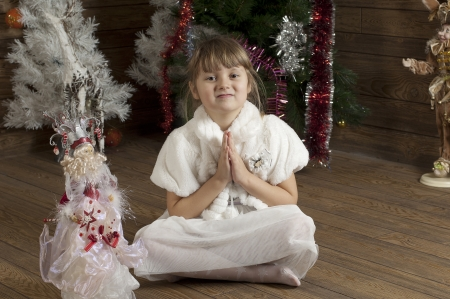 troll dolls: Photo of girl sitting on a floor in New Year room decorated Stock Photo