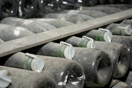 Stack of wine bottles in winery. Champagne wine storage