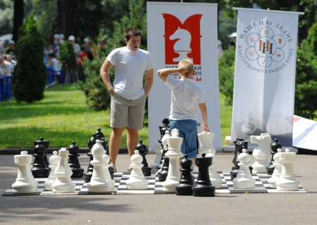 MOSCOW - JULY 13  Unidentified man and kid playing big street chess on city event Sport of Moscow passing in Luzhniki, on July 13, 2013, in Moscow, Russia