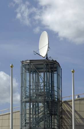 intercommunication: Satelite on a roof against blue sky with white clouds