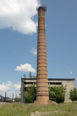 tall chimney: Brick built tall industrial chimney against blue cloudy sky